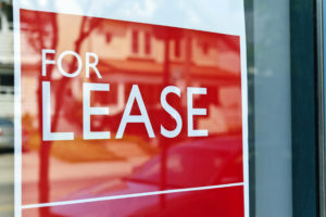 For Lease sign on red in window reflecting street scene